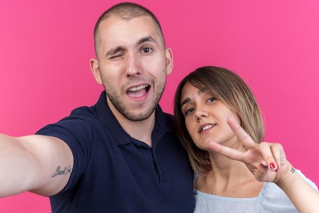 Jeune beau couple homme et femme heureux et positif souriant montrant gaiement le signe v debout sur le mur rose