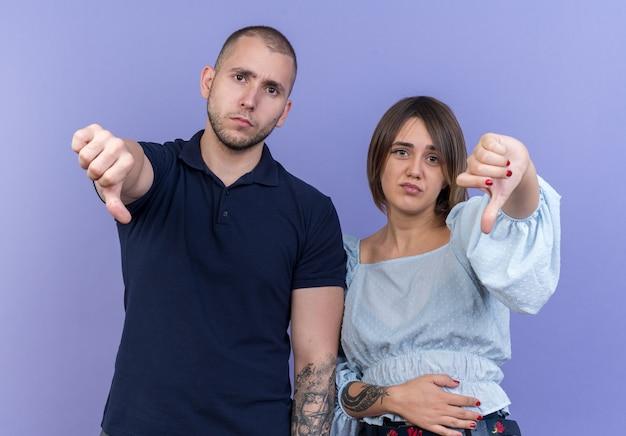 Jeune beau couple homme et femme mécontent montrant les pouces vers le bas debout sur le mur bleu
