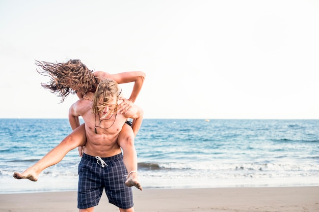 Jeune beau couple homme et femme à la plage jouant et s'amusant ensemble dans le bonheur