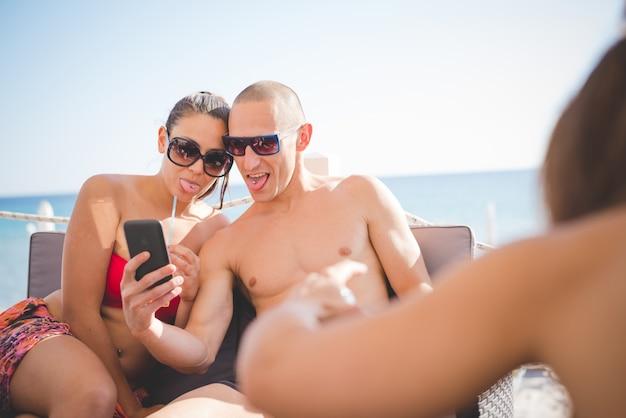 Jeune beau couple homme et femme prenant selfie au bar de la plage en été
