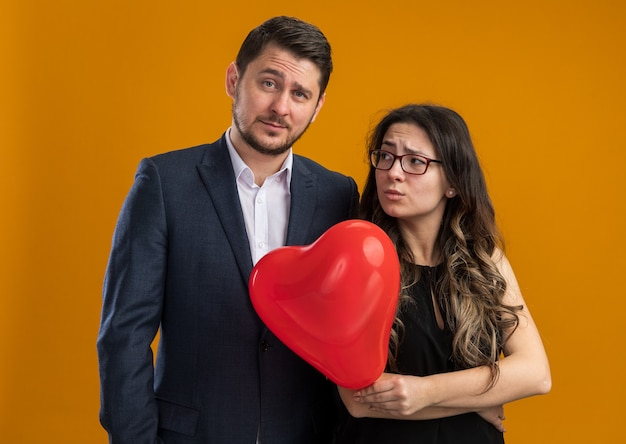 Jeune et beau couple homme et femme rancunière avec ballon rouge en forme de coeur debout l'un à côté de l'autre célébrant la saint-valentin