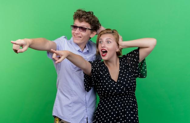 Jeune beau couple homme et femme regardant de côté surpris en pointant avec l'index à quelque chose debout sur le mur vert
