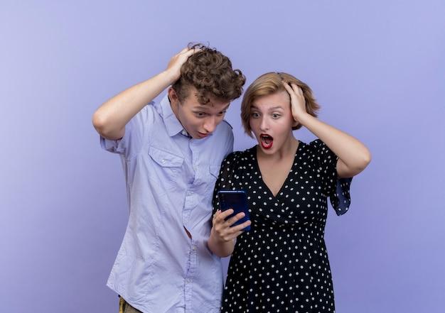 Jeune beau couple homme et femme regardant l'écran du smartphone surpris et étonné debout sur le mur bleu