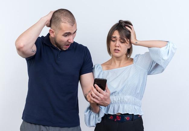 Jeune beau couple homme et femme avec smartphone le regardant confondu avec les mains sur la tête debout