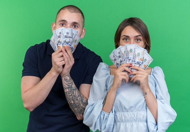 Jeune beau couple homme et femme tenant de l'argent à l'air étonné et surpris debout
