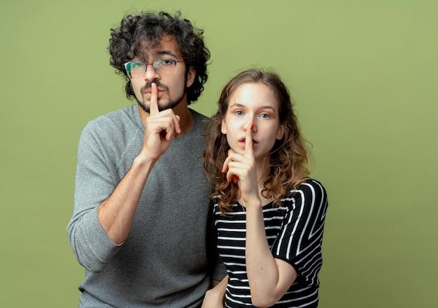 Jeune beau couple homme et femmes regardant la caméra en faisant un geste de silence avec les doigts sur les lèvres sur fond vert clair