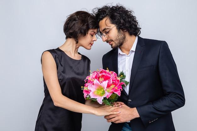 Jeune beau couple homme heureux donnant un bouquet de fleurs à sa charmante petite amie heureuse en amour célébrant la journée internationale de la femme le 8 mars debout sur fond blanc