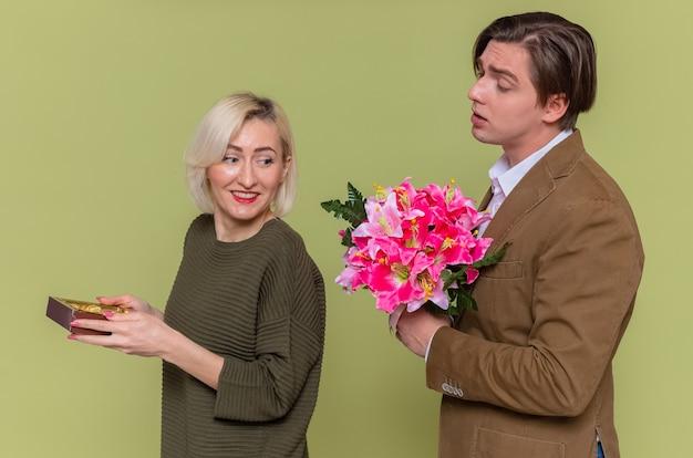 Jeune beau couple homme heureux donnant un bouquet de fleurs à sa petite amie souriante avec boîte de bonbons au chocolat célébrant la journée internationale de la femme debout sur le mur vert