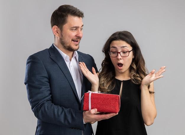Jeune beau couple homme heureux donnant un cadeau pour sa charmante petite amie excitée heureuse en amour célébrant ensemble la saint-valentin