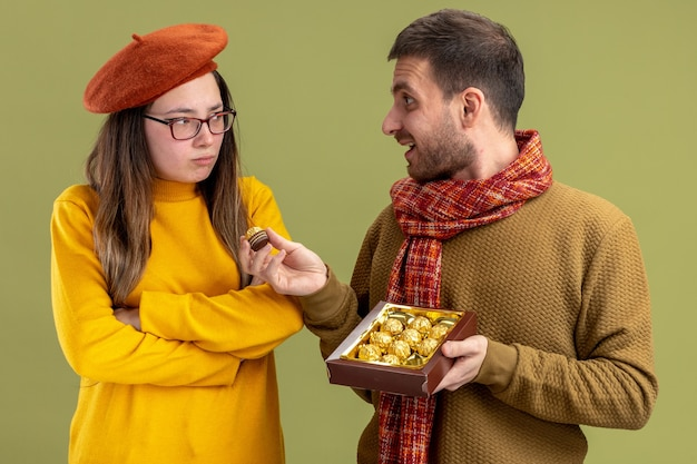 Jeune beau couple homme heureux offrant des bonbons au chocolat à sa petite amie offensée en béret célébrant la saint-valentin debout sur le mur vert