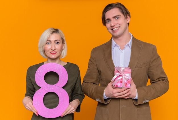 Jeune beau couple homme heureux avec présent et femme tenant le numéro huit
