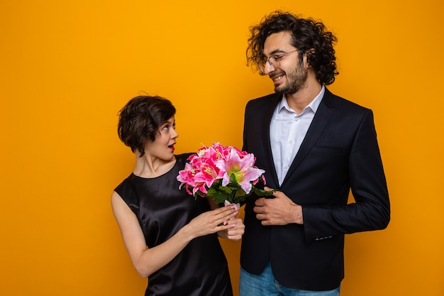 Jeune beau couple homme heureux en regardant sa petite amie surprise avec bouquet de fleurs souriant joyeusement heureux en amour célébrant la journée internationale de la femme