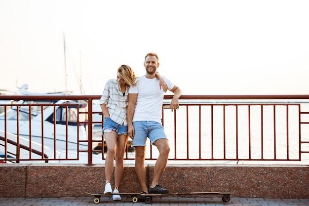 Jeune beau couple marchant au bord de mer, souriant, planche à roulettes.