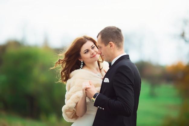 Jeune beau couple de mariage de femme en robe longue blanche et voile et homme en costume formel noir debout ensemble dans la forêt vert foncé sur fond naturel, photo horizontale