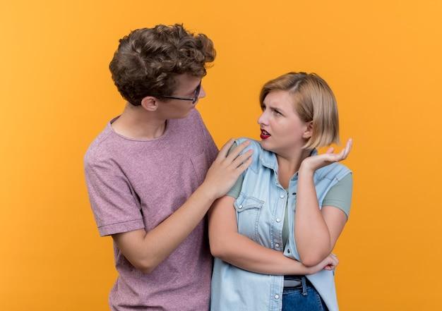 Jeune beau couple portant des vêtements décontractés homme demandant pardon femme mécontente après combat debout sur le mur orange