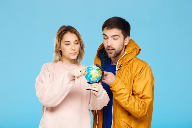 Jeune beau couple posant en pointant vers différents endroits du petit globe sur mur bleu