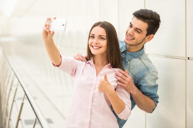 Jeune beau couple prenant selfie avec smartphone.