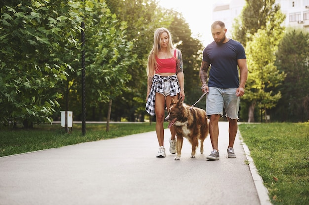 Jeune beau couple promener le chien dans le parc d'été