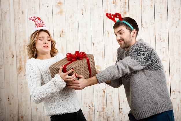 Jeune beau couple se battre pour un cadeau de noël sur un mur en bois