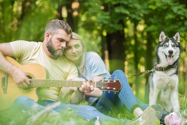 Jeune et beau couple se détendre dans la nature avec un chien à la guitare