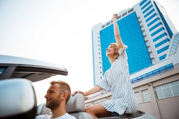 Jeune beau couple souriant, assis dans la voiture près de la mer.