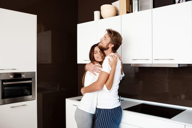 Jeune beau couple souriant embrassant debout à la cuisine.