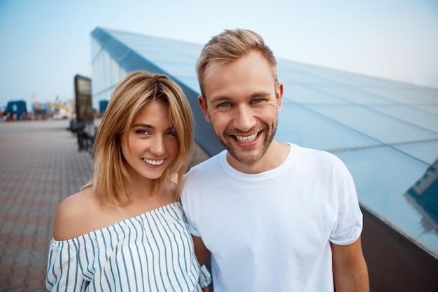 Jeune beau couple souriant, embrassant, se promenant dans la ville