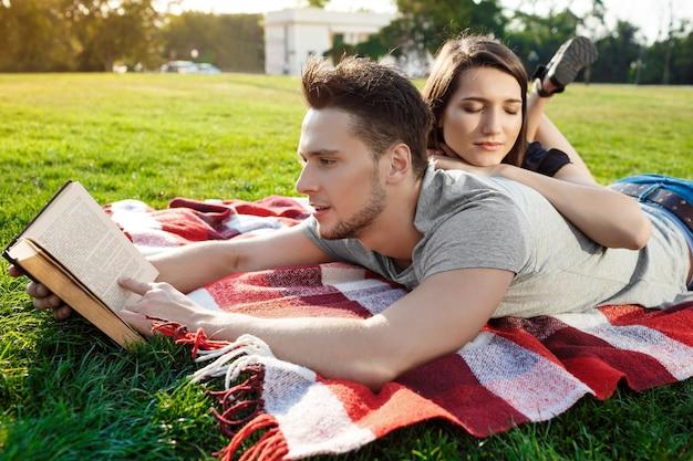 Jeune beau couple souriant lecture au parc.