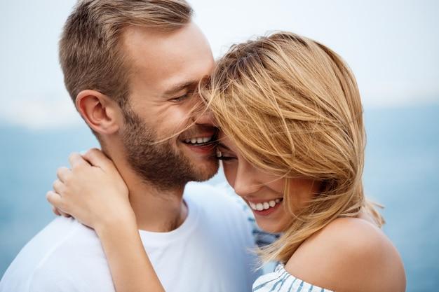 Jeune beau couple souriant, se réjouissant, vue sur la mer.