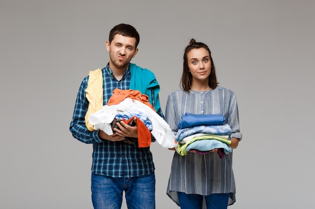 Jeune beau couple tenant des vêtements de lavage sur mur gris