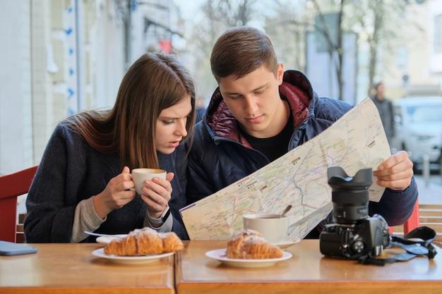 Jeune beau couple de touristes se reposant au café en plein air