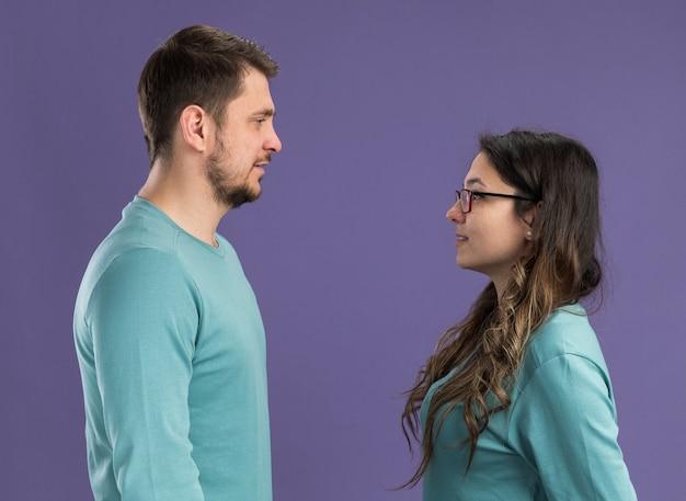 Jeune beau couple en vêtements décontractés bleus homme et femme heureux et joyeux se regardant heureux amoureux debout sur un mur violet