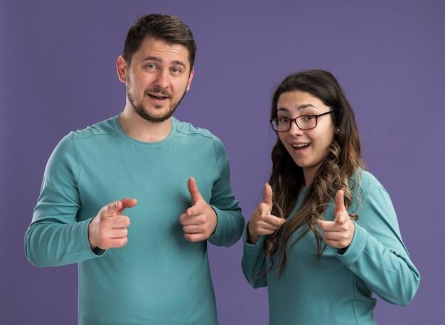 Jeune beau couple en vêtements décontractés bleus homme et femme souriant pointant gaiement avec des index heureux en amour debout sur un mur violet