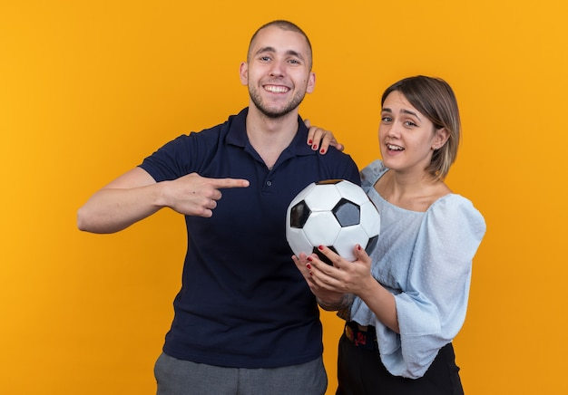Jeune beau couple en vêtements décontractés femme souriante tenant un ballon de football tandis que son petit ami souriant pointant avec l'index sur le ballon debout sur le mur orange