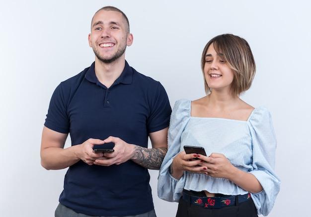 Jeune beau couple en vêtements décontractés homme et femme heureux et positif tenant des smartphones regardant de côté avec le sourire sur le visage debout