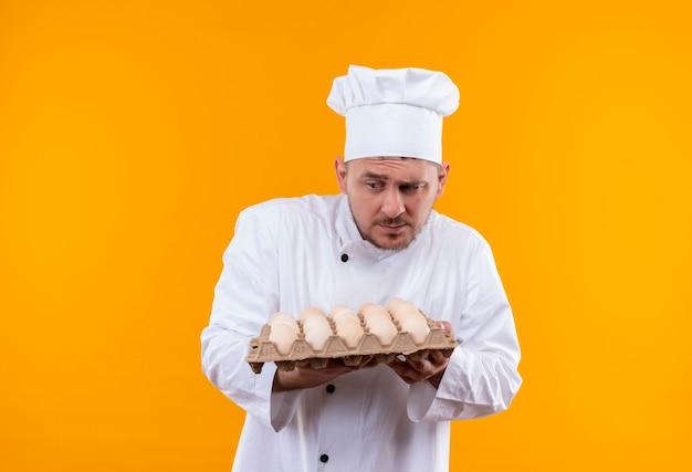Jeune beau cuisinier confus en uniforme de chef tenant un carton d'œufs regardant le côté isolé sur un mur orange