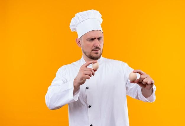 Jeune beau cuisinier confus en uniforme de chef tenant et regardant des œufs isolés sur un mur orange