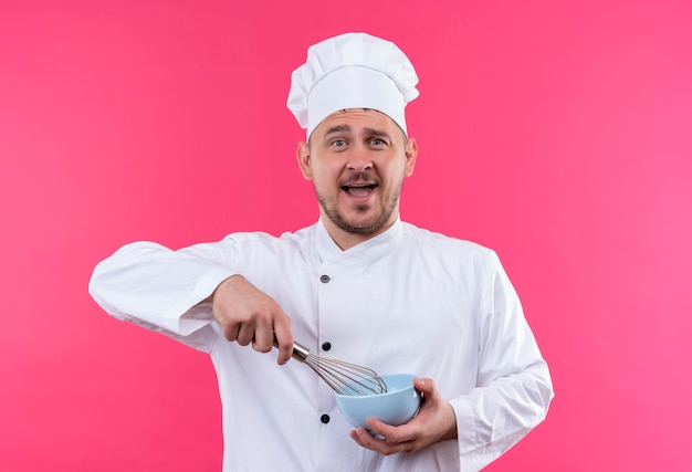 Jeune beau cuisinier impressionné en uniforme de chef tenant un fouet et un bol isolé sur un mur rose