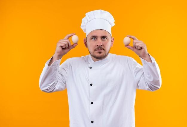 Jeune beau cuisinier impressionné en uniforme de chef tenant des œufs isolés sur un mur orange