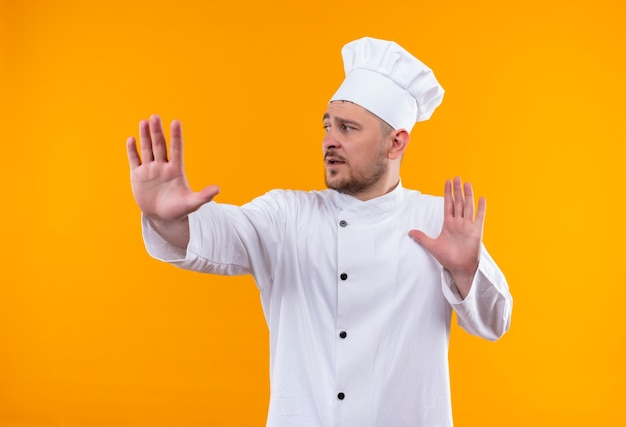 Jeune beau cuisinier en uniforme de chef qui s'étend la main à côté isolé sur l'espace orange