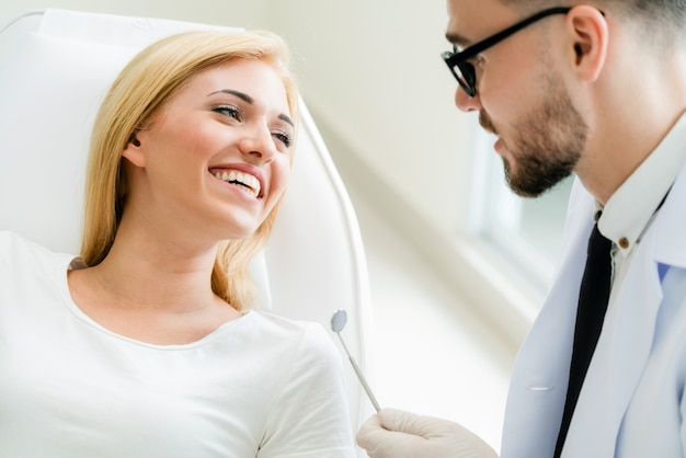 Jeune beau dentiste parle avec une patiente heureuse assis sur une chaise de dentiste dans une clinique dentaire.