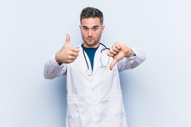 Jeune beau docteur homme montrant les pouces vers le haut et les pouces vers le bas, difficile choisir le concept