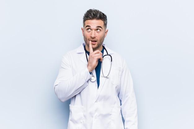 Jeune beau docteur homme regardant de côté avec une expression douteuse et sceptique