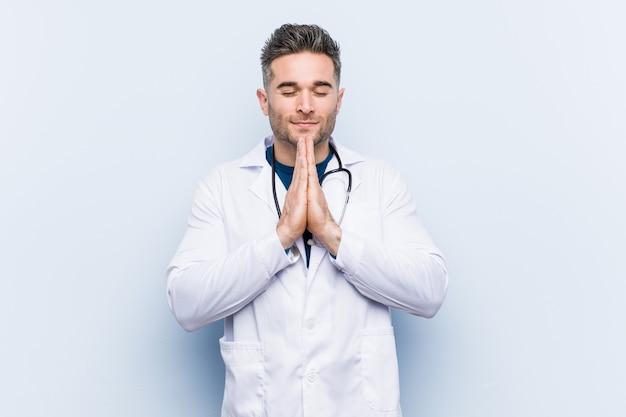 Jeune beau docteur homme tenant la main dans prier près de la bouche, se sent confiant.