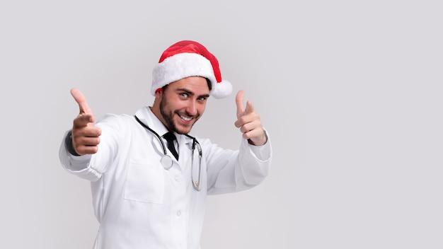 Jeune beau docteur en uniforme blanc et chapeau de père noël