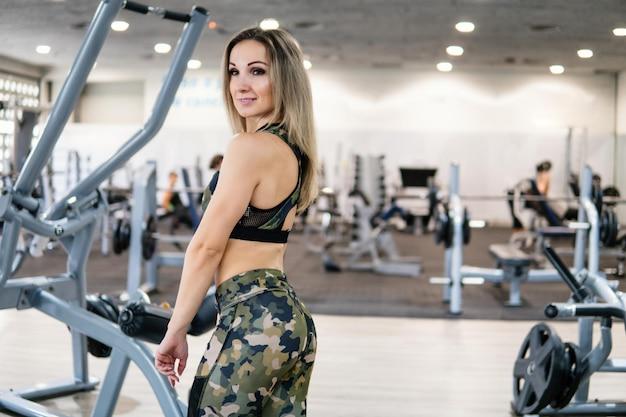Jeune et beau entraîneur de fitness posant devant la caméra dans la salle de gym. puissance de l'entraîneur