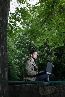 Jeune beau étudiant assis sur un banc en bois dans le parc avec ordinateur portable.