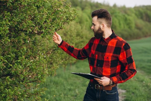 Jeune beau fermier barbu avec dossier debout dans un jardin de fruits verts au début du printemps