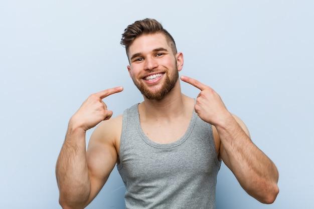 Jeune beau fitness homme sourit, pointant les doigts sur la bouche.