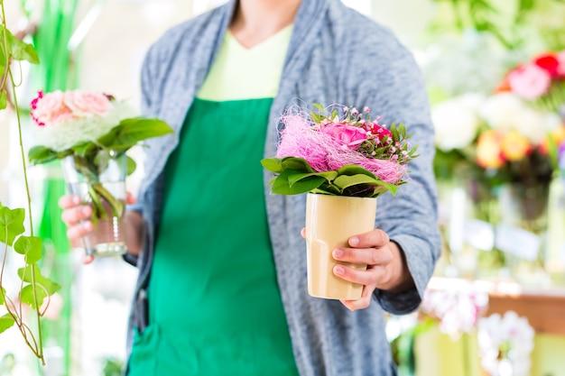 Jeune beau fleuriste vendant des fleurs et des bouquets en boutique